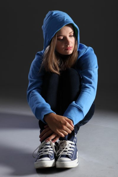 Blonde teenager girl alone and sad in blue hoodie